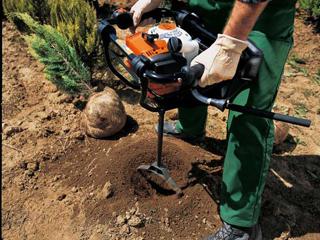 Бензобур работает в грунте на участке