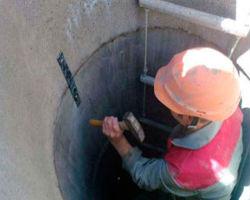 Рабочий выполняет скрепление бетонных колец для последующего углубления колодца