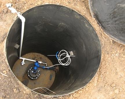 Вкопанный кессон с подключенным оборудованием для скажины