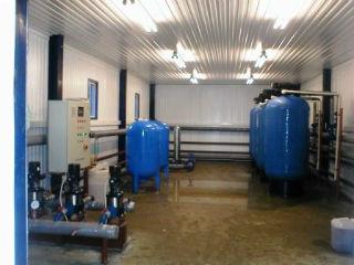 Система водоподготовки с панелью управления и крупными накопительными баками.