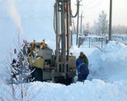 Автомобильная буровая установка выполняет работы по разработке скважины в зимнее время года