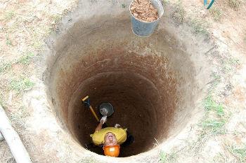 Выработка грунта из котлована под колодец