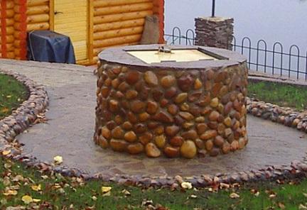 Обустроенный круглый колодец, отделанный камнем, с крышкой