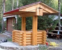 Обустроенный колодец с двускатной крышей на дачном участке