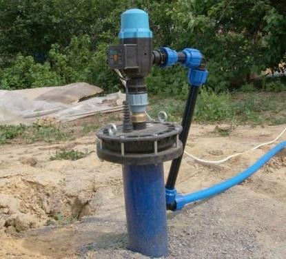 Оборудованная скважина на дачном участке с насосом
