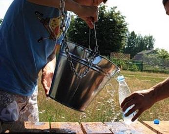 Процесс отбора воды из колодца для анализа