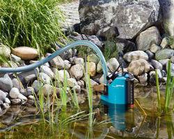 Обычный дренажный насос во время откачки жидкости из загрязненного пруда